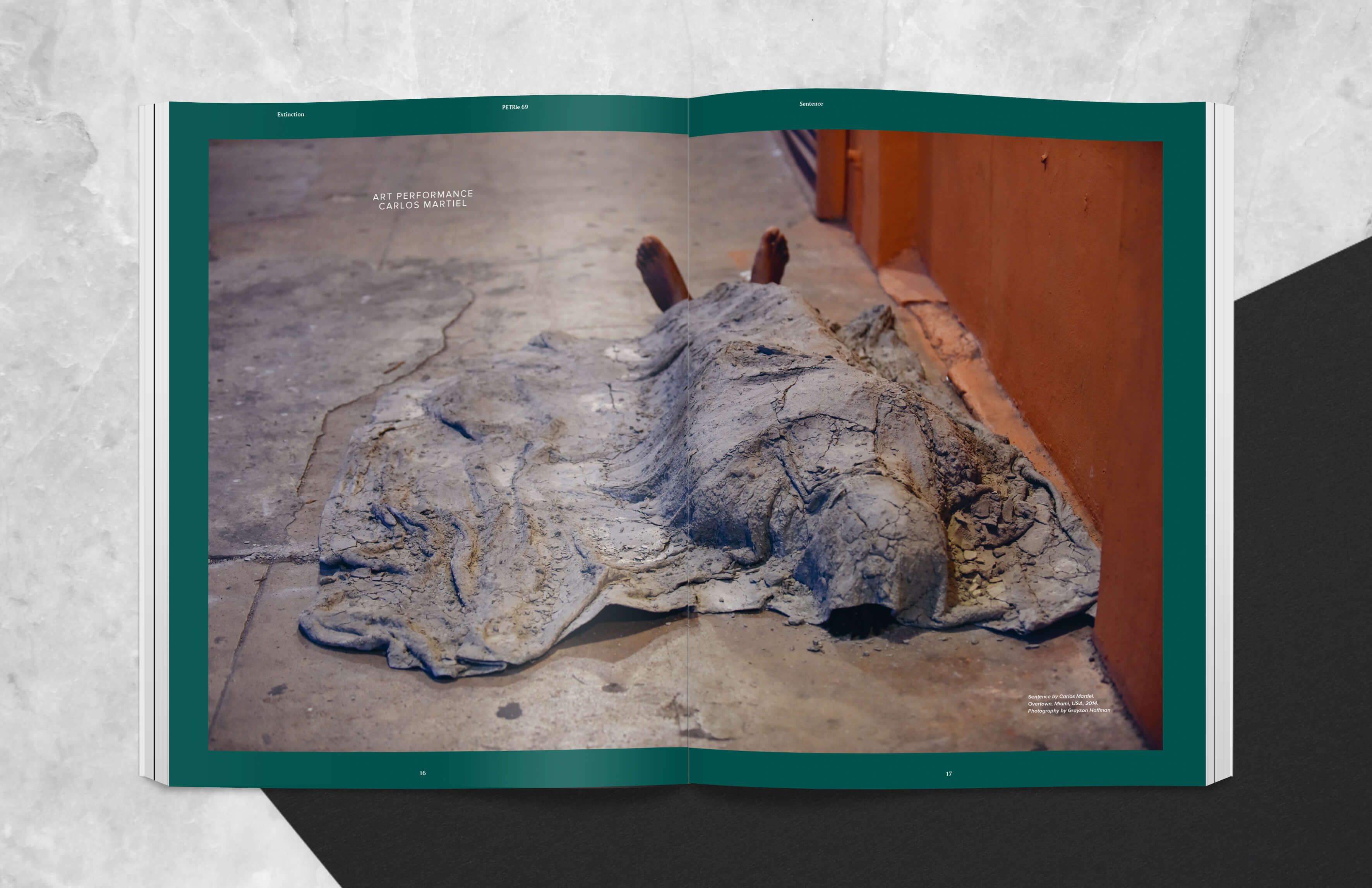 Magazine spread showing art performance, body under concrete blanket