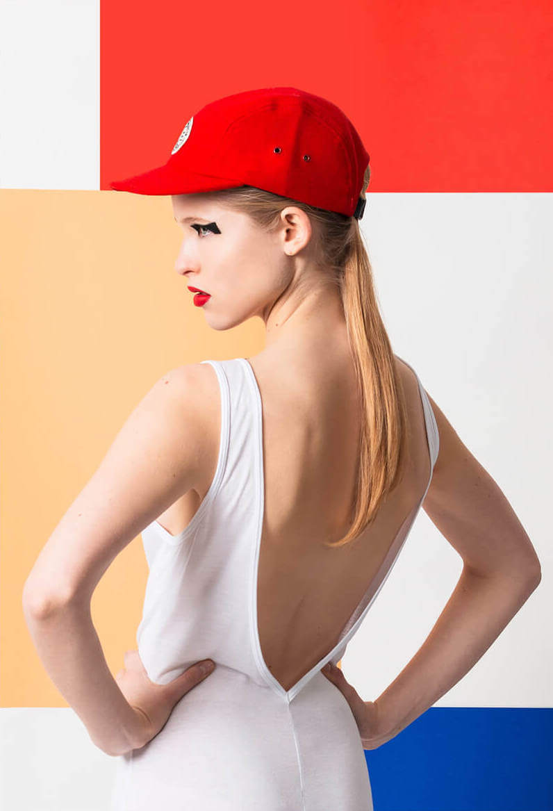 Female model with hat in front of colourful bauhaus background
